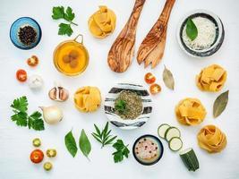 italiensk mat koncept och meny design. torkad fettuccine med träspatel och ingredienser söt basilika, tomat, vitlök, persilja, lagerblad, peppar och zucchini på vit träbakgrundsläge. foto