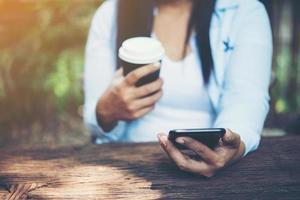 kvinnans hand som håller en smartphone foto