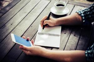 närbild av affärsmannen som använder smartphonen medan han arbetar på café foto