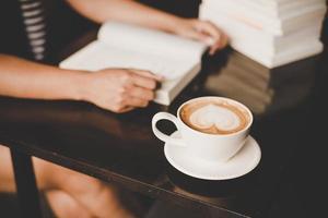 kvinna som kopplar av och läser en bok på ett kafé foto