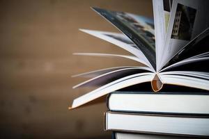 öppen bok, bunt med inbundna böcker på träbord foto