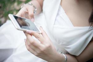 flicka sitter med smartphone i händerna foto