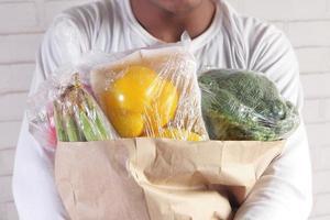 bär grönsaker i en brun påse foto