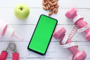 smart telefon med sportutrustning foto
