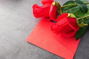 rött kuvert och röda rosor foto