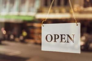 ett affärsskylt som säger öppen hängande på dörren vid ingången