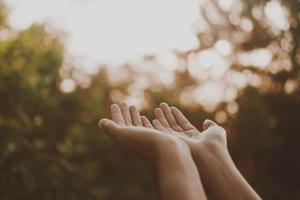händer placerade tillsammans som att be framför naturens gröna bakgrund