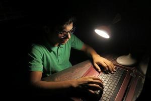 man som arbetar vid ett skrivbord på natten foto