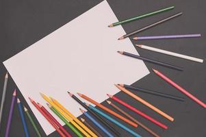 flerfärgade pennor och vitt papper på svart bakgrund foto