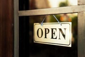 ett affärsskylt som säger öppna på dörren vid ingången