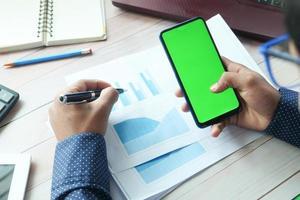 man använder en smart telefon på ett skrivbord
