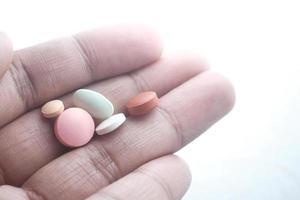 närbild av färgglada piller i handen isolerad på vit foto
