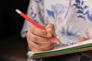 närbild på en hand som skriver med en röd penna