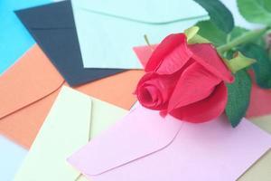 konstgjord ros med färgglada kuvert foto