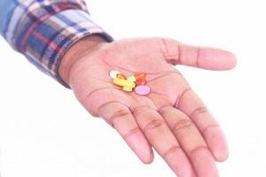 man som håller piller på vit bakgrund