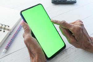 äldre kvinnas hand med smart telefon