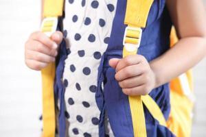 flicka med gul ryggsäck foto