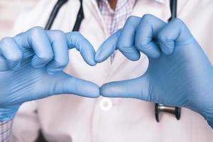händer som bär handskar som håller hjärtaform foto