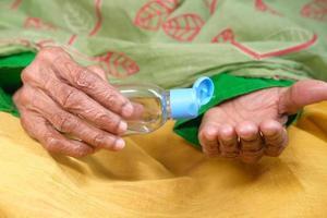 gammal kvinna med handdesinfektionsmedel foto