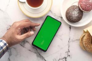 ovanifrån av en smart telefon med frukost foto