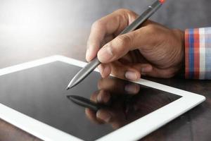 man som använder pennan på den digitala minnestavlan foto