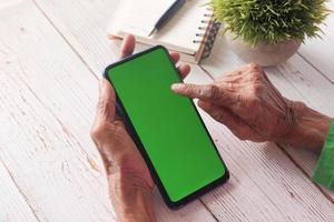 person som använder smart telefon med grön skärm foto