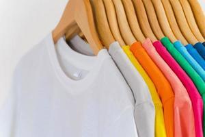 närbild av t-tröjor på galgar, klädbakgrund foto