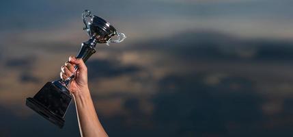 en man som håller upp en trofékopp mot molnig skymninghimmelbakgrund foto