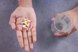 hand som håller piller och ett glas vatten foto