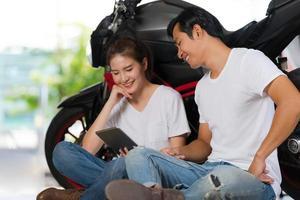 lyckliga par som använder den digitala minnestavlan hemma med en motorcykelbakgrund foto