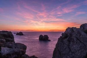 solnedgång på den steniga stranden