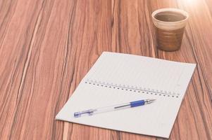 anteckningsbok och kaffe på skrivbordet foto