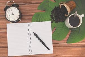 anteckningsböcker och kaffemuggar på skrivbordet foto