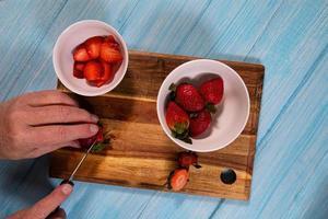 ovanifrån av en person som skivar jordgubbar foto