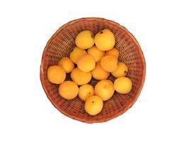 aprikoser i en flätad korg på vit bakgrund foto