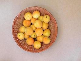 aprikoser i en flätad korg på bordsbakgrund foto