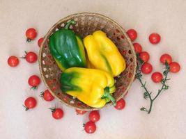 paprika i en flätad korg bredvid tomater på en beige tabellbakgrund foto