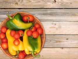 paprika och tomater i en flätad korg på en träbordbakgrund foto