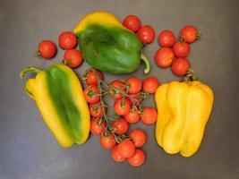 paprika och tomater på en mörk tabellbakgrund foto