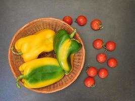 paprika i en flätad korg bredvid tomater på en mörk tabellbakgrund foto