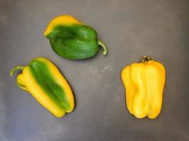 gröna och gula paprika på en träbord bakgrund foto