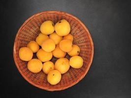 aprikoser i en flätad korg på mörk bordsbakgrund foto