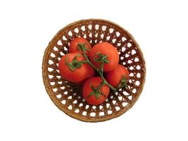 tomater i en flätad korg på en vit bakgrund foto