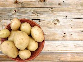potatis i en rotting korg på en träbord bakgrund foto