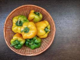 gröna och gula paprika i en flätad korg på en träbordbakgrund