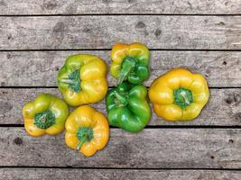 gröna och gula paprika på en träbord bakgrund