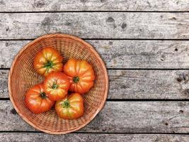 tomater i en rotting korg på en träbord bakgrund foto