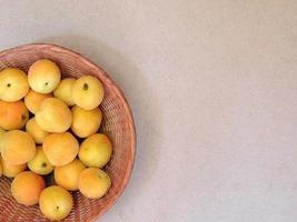 aprikoser i en flätad korg på beige bakgrund foto