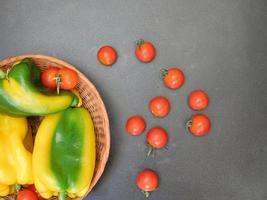 paprika och tomater i en flätad korg på en mörk tabellbakgrund foto