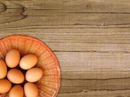 bruna ägg i en rotting korg på träbord bakgrund foto